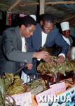 图文:两名男子非洲食品节上品尝芭蕉鸡