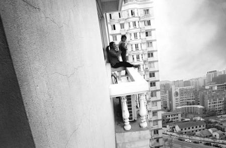 图文:母亲抓着孩子坐在十七楼窗台上