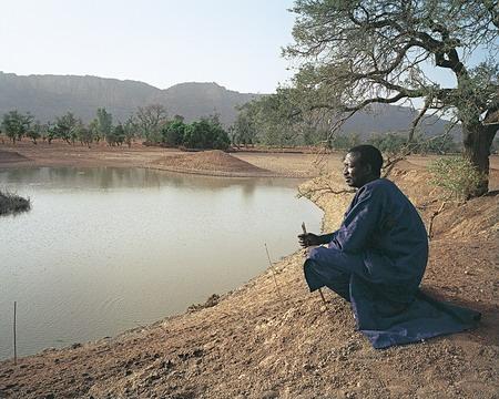 图文:蹲在池塘边的渔夫