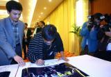 图文:评委沙希都在华赛大奖作品上签名