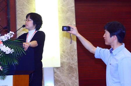 图文:摄影师在台下拍摄论坛主持人黄文