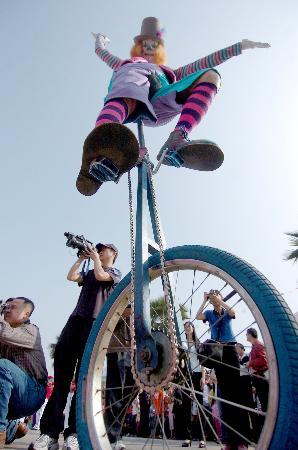 图文:小丑演员在广西小丑节表演骑独轮车