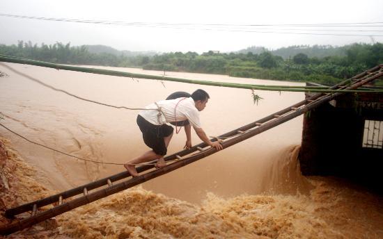 图文:广东紫金县工作人员爬上水闸准备开启阀门