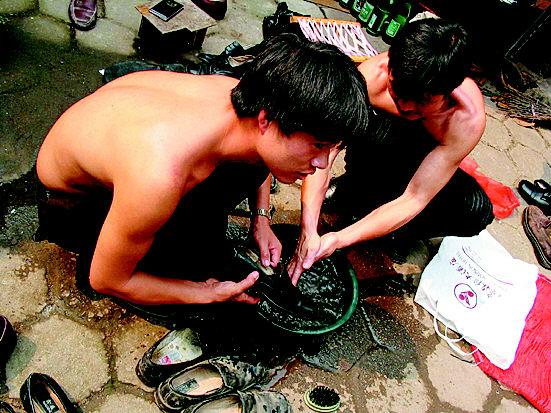 不法商贩正在清洗旧皮鞋.非法翻新旧鞋的窝点