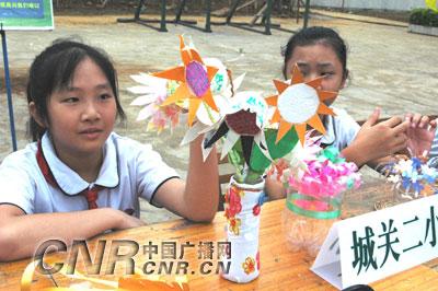 ):邕宁区的中小学生在展示他们用废旧饮料瓶、易拉罐和包装纸品