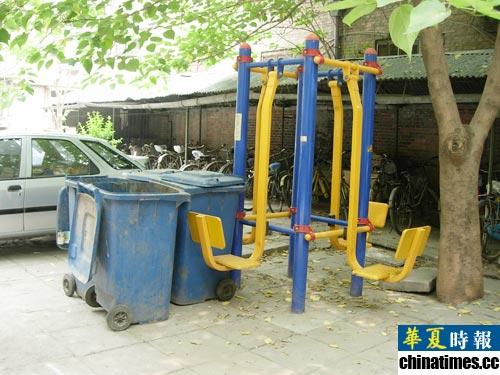 4个脏兮兮的蓝色大垃圾桶紧靠着健身器材.垃圾桶周围苍蝇乱飞,