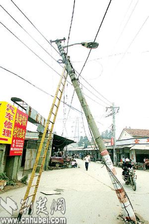 汉口二七路一电杆根底部破裂 歪向水果店