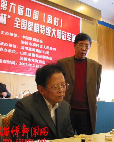 淄博嘉周集团董事长卢令良(右)在观看胡荣华和洪智的