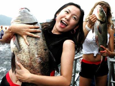 6月21日,香港旅游小姐(前)怀抱千岛湖渔民捕获的一条大鱼.