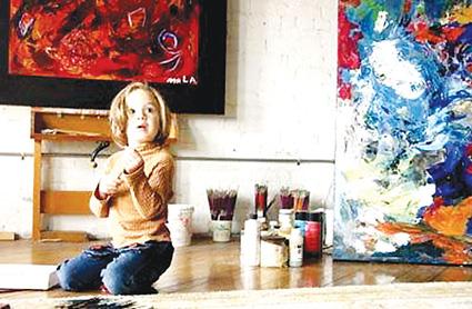 玩画笔,旁边的抽象画就是她的大作.-美4岁女童成为画家 卖画收入