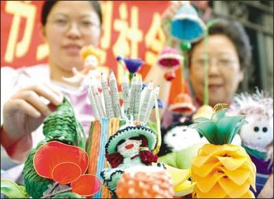 社区群众用废报纸制作环保铅笔,用旧丝袜制作工艺品,玩具等.