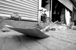 徐胤/一把打砸超市时用的铁锨留在现场。本报记者徐胤摄