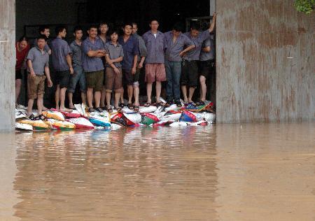图文:工人们用沙袋堵住雨水进入仓库