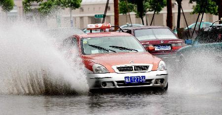 图文:一辆出租车在积水的马路上前行