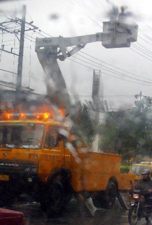 图文:工作人员冒雨抢修一处被大风刮坏的电线
