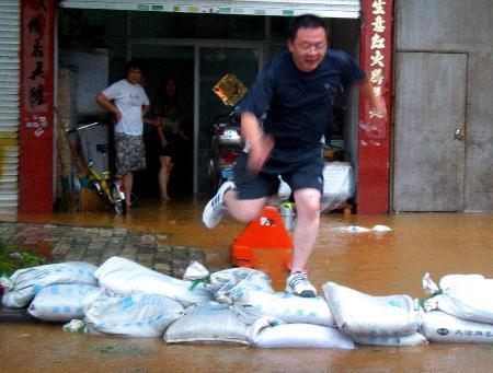 图文:一男子纵身跳过路桥城郊一处积水坑