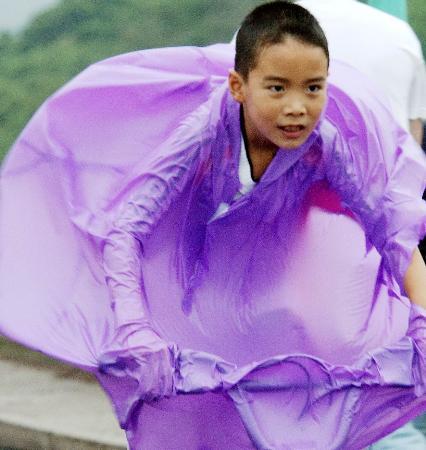 图文:杭州一名男孩在风中艰难骑行