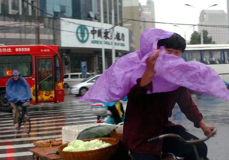 图文:骑车人的雨衣被大风刮起
