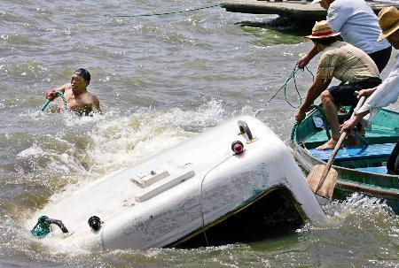图文:工作人员在打捞被风浪击沉的游船