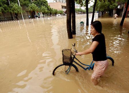 图文:市民在福州市内被淹没的道路上涉水而行