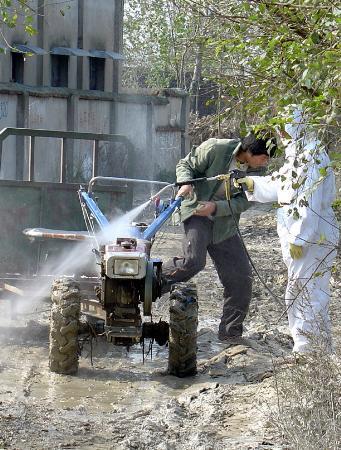 图文:工作人员对进出疫区的车辆人员进行消毒