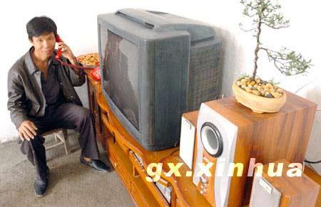 在广西象州县中平镇大淮灾民新村,一位住上新房的灾民拿着新装的电话