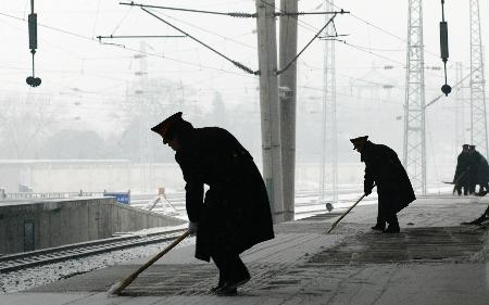 图文:北京西站工作人员在清扫站台上的积雪