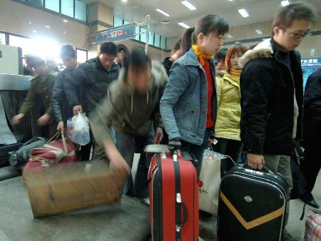 图文:学生在郑州火车站进站口接受安检