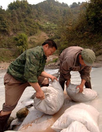 图文:两名民工正在挪动土包筑坝