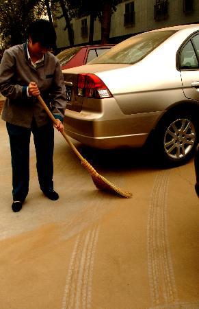 图文:保洁员在清扫地上的沙土