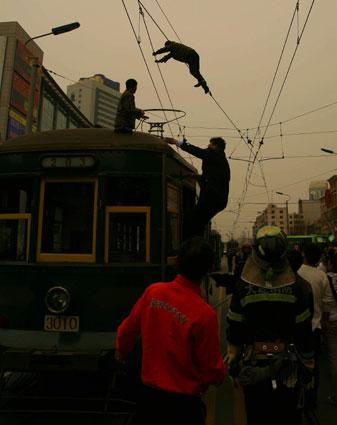 男子精神失常四处撒钱并爬上电车缆线(组图)