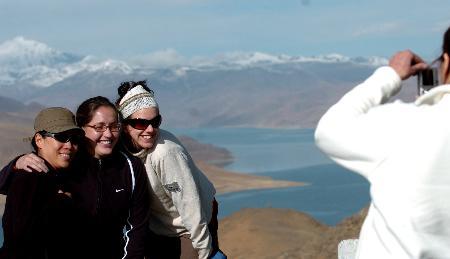 图文:外国游客在美丽的羊卓雍湖前留影