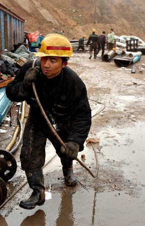 图文:救援人员在雨中向井下水泵移机输送钢缆