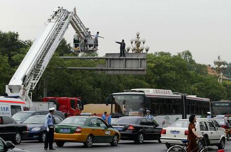 组图:男子携匕首爬上北京交通指示牌引起塞车