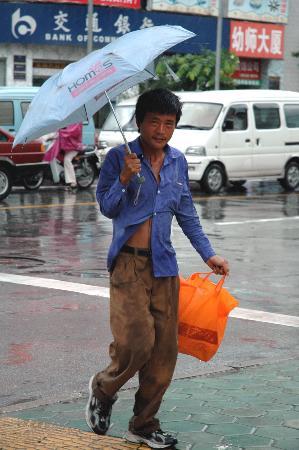 图文:广西南宁街头一行人在大风中行走
