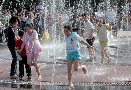 图文:市民在郑州紫荆山公园广场喷泉边戏水