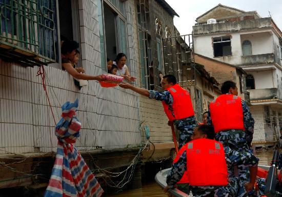 图文:救援人员在为被洪水围困的群众分发食物