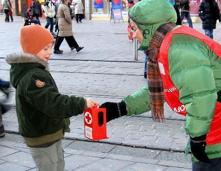 图文:一名男孩将零花钱投入捐款盒