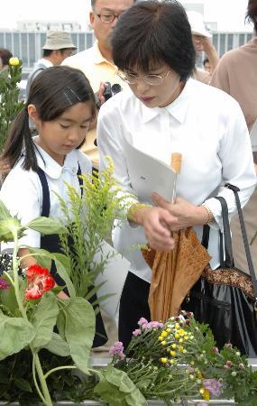 图文:一对母女向原子弹爆炸受害者献花