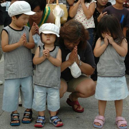 图文:女子带着三个孩子悼念原子弹爆炸受害者