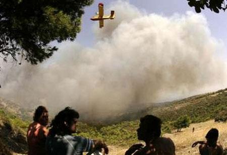 图文:当地人望着空中的特种灭火飞机