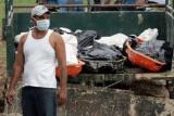 图文:一名救援人员站在装满乘客遗体的卡车旁