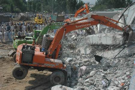 图文:救援人员用挖掘机清理废墟
