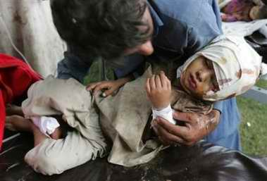 图文:巴基斯坦男子抱着受伤儿子