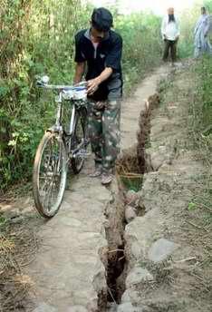 图文:一名印度男子骑车经过布满地震裂缝道路