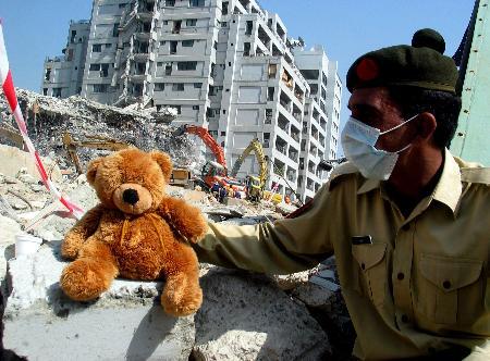 图文:一名救援人员正在查看一只玩具熊
