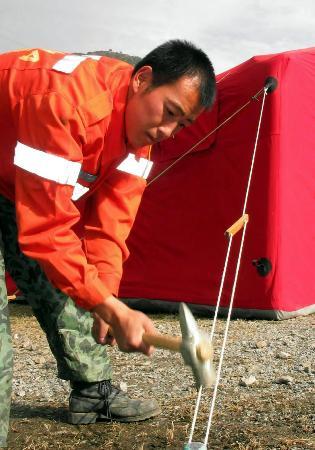 图文:一名中国国际救援队队员在重新固定帐篷