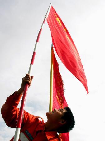 图文:中国国际救援队队员正在竖立旗杆