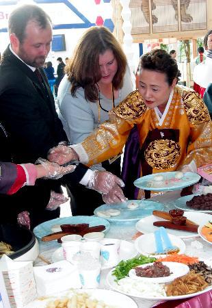 图文:两名外国参观者参与制作一种韩国糕点