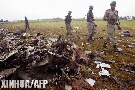 图文:几名警察从一堆飞机残骸旁走过